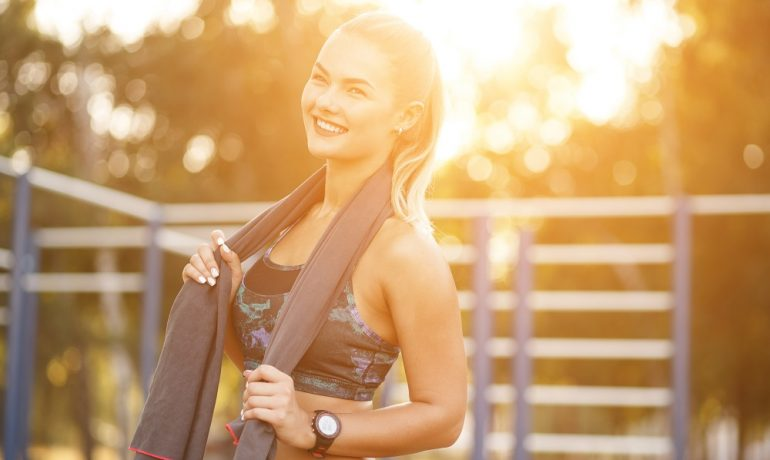 Smiling sport woman using towel while resting on the sport ground. Handsome Active Woman With Fit Muscular Body Resting After Workout Exercises. Sporty Athletic Female sits in the park, Training Outdoor.